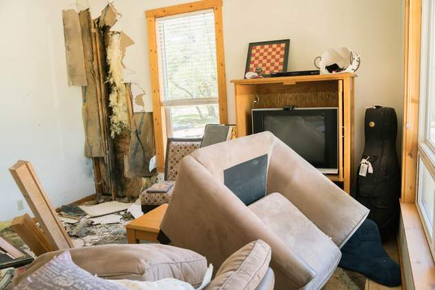 A loveseat flew across Brett and Rachel Fedor's livingroom, while the music stand and cello remain unmoved, during a lightning strike at their home April 18. The strike destroyed sections of the roof and started a fire in their second floor master bathroom.