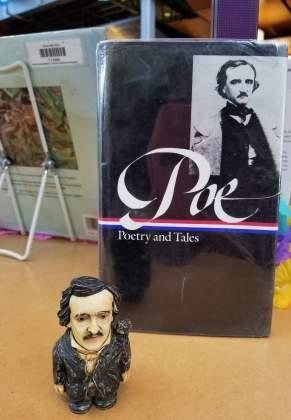 Mini-Edgar Allan Poe figurine on display at the library.