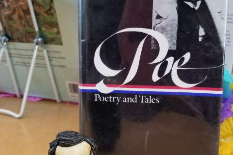 Mini-Edgar Allan Poe figurine on display at the library.