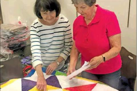 Bonnie Gates, left, and Alice Hobbs check in quilts for Saturday's Hauptstrasse Quiltfest.