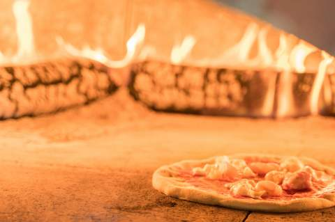 A D.O.P Magherita Pizza- Buffalo mozzarella, yellow Mt. Vesuvius cherry tomatoes and San Marzano tomato sauce bubbles in a 700 degree Fahrenheit brick oven for only a few minutes before it rises to perfection and is ready to eat.