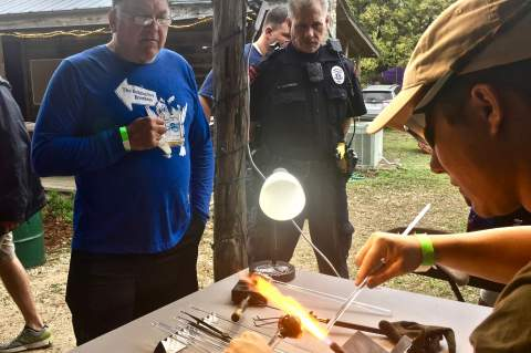 Charlie Pavlich and Boerne PD detective Clay Norbery watch as artist Justin Ashley shapes a glass creation. Star photo by Elena Tucker